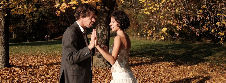 Tanzpaar im goldenen Herbstlaub. Sie stehen einander gegenüber und sind im Profil sichtbar. Die gefassten Hände im Vordergrund sind flach aneinander gehalten, die hinteren gefasst.