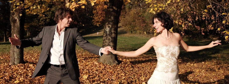Tanzpaar im Ballgewand im goldenen Herbstlaub. Sie stehen mit Abstand seitlich nebeneinander. Beide strecken die Arme seitlich weg. Die inneren Hände sind gefasst, beide schauen sich an