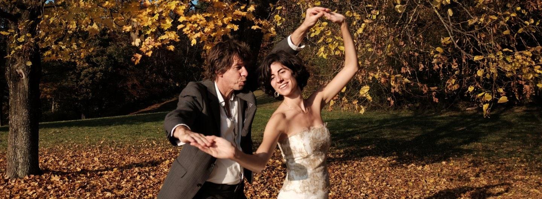 Tanzpaar im goldenen Herbstlaub. Sie steht mit dem Rücken zu ihm, beide Hände sind gefasst die hinteren sind über die Köpfe gehalten, die vorderen in Brusthöhe. Sie strahlt er spitzt die Lippen