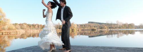 Tanzpaar im Balloutfit auf einem Steg am See. Sie dreht unter seinem rechten Arm, der Rock und die Haare fliegen durch die Drehbewegung. Beide lachen