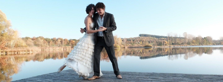 Tanzpaar im Balloutfit auf einem Steg am See. Im Hintergrund herbstliche Laubbäume. Sie steht in seinem rechten Arm das rechte Bein weggesteckt die gefassten Hände vor seinem Körper