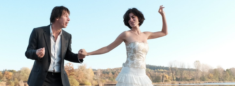 Tanzpaar im Balloutfit, im Hintergrund blauer Himmel und herbstliche Laubbäume. Sie steht auf seiner linken Seite, die zugewandten Hände gefasst, ihre linke Hand hält sie abgewinkelt zum Himmel, er schnipst mit seiner freien Hand