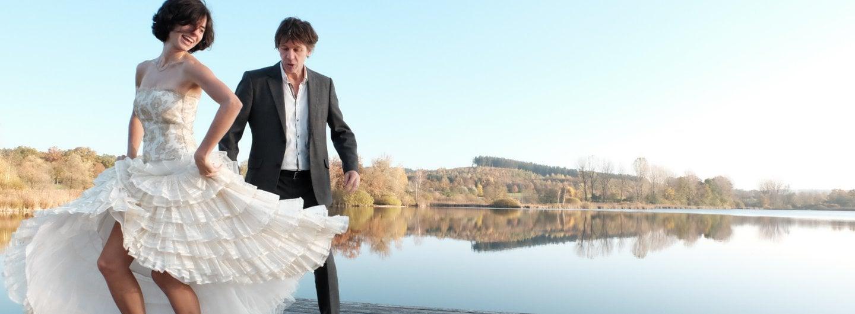 Tanzpaar im Balloutfit vor blauem Himmel und herbstlichen Laubbäumen. Sie steht mit dem rücken zu ihm, rafft ihren Rock und schaut über ihre linke Schulter zurück, Er schaut auf ihren Rock
