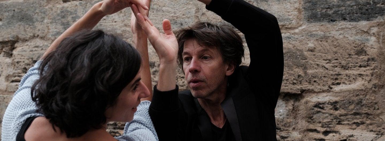 Tanzpaar vor Stadtmauer. Er trägt ein schwarzes Sacko, sie einen hellblauen Strickpulover der nur bis zum Ellenbogen reicht. Sie lächelt er schaut konzentriert. Sie haben die beiden rechten und linken Hände gefasst und zu zwei Toren erhoben und stehen sich gegenüber.