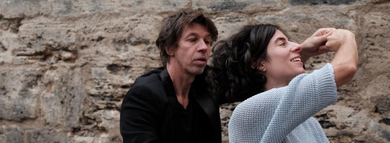 Tanzpaar vor Stadtmauer. Sie dreht unter seiner linken und ihrer rechten Hand durch. Er trägt ein schwarzes Sacko, sie einen hellblauen Strickpulover der nur bis zum Ellenbogen reicht. Sie lächelt er schaut konzentriert