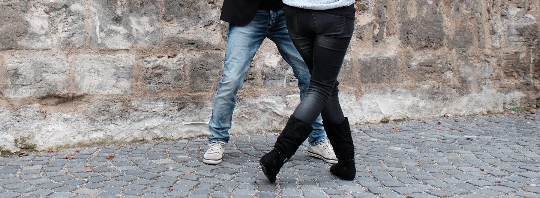 Ein Tanzpaar ab der Hüfte abwärts auf einem Kopfsteinpflaster vor einer Steinmauer. Sie trägt eine schwarze Jeans, schwarze Stiefel und ein blaues Oberteil. Er weiße Sneaker, Bluejeans, schwarzes Oberteil und Sakko. Er steht in einer Grätsche, sie vor ihm mit dem rechten Bein vor dem linken in Schrittstellung gekreuzt