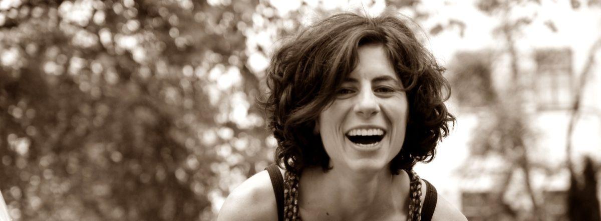 Portraitfoto einer lachenden Frau mit schwarzen lockigen Haaren und Blick in die Kamera. Im Hintergrund sind verschwommen Laubbäume zu sehen