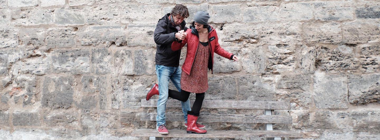 Tanzendes Paar vor Stadtmauer auf Parkbank.