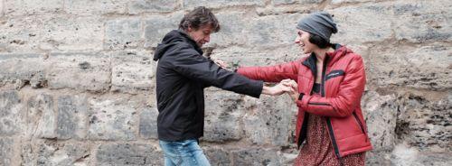 Tanzpaar vor Stadtmauer.Sie trägt eine rote Jacke und graue Mütze, sowie ein rotgepunktetes Kleid. Sie hat schwarze Haare und lächelt ihn an. Er trägt eine schwarze Kapuzenjacke, und Bluejeans, einen Schal in den Farben dunkel-, hellgrau und rostrot. Er hat braune Haare, eine Kurzhaarfrisur und blickt zu Boden. Sie stehen sich gegenüber seitlich zur Kamera. Seine linke und ihre rechte Hande sind gefasst, sein Arm gebeugt, ihrer gestreckt, mit den anderen Händen ist es genau anders herum.