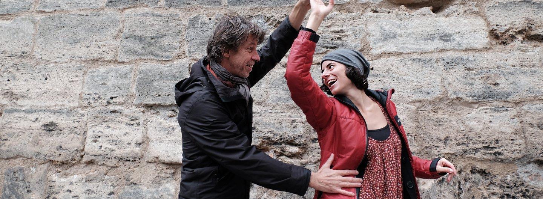 Tanzendes Paar in herbstlicher Kleidung vor Stadtmauer. Sie dreht unter seinem Arm durch, seine zweite Hand liegt an ihrer Taille