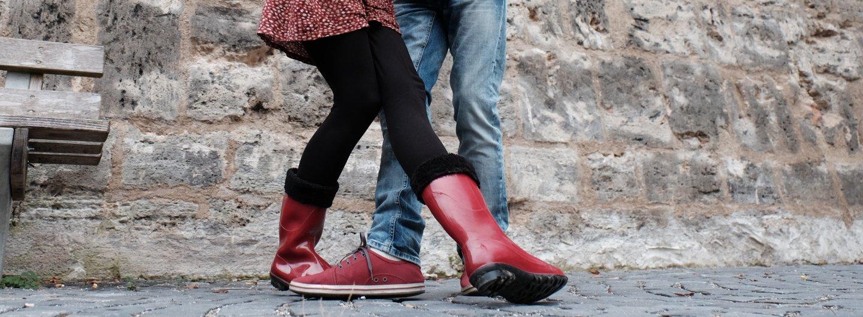 rote Gummistiefel und rote Sneaker in verschränkter Tanzposition vor Stadtmauer und neben einer Sitzbank