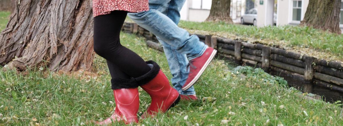 Grüne Wiese, mit getrocknetem Laub und einem Baum mit gefurchter Rinde im Hintergrund. Auf der Wiese sind ab der Hüfte abwärts zwei laufende Paar Beine zu sehen. Sie steckt in roten Gummistiefeln, schwarzer Leggins und rot gepunktetem Kleid, er trägt rote Sneakers und eine Bluejeans