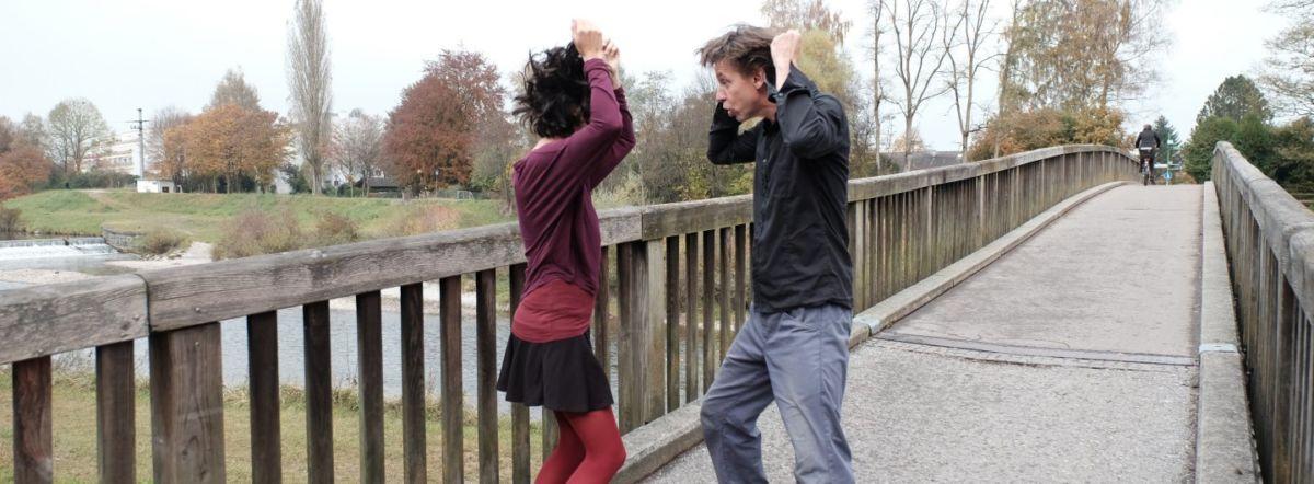Paar steht voreinander auf einer Brücke und rauft sich tanzend die Haare
