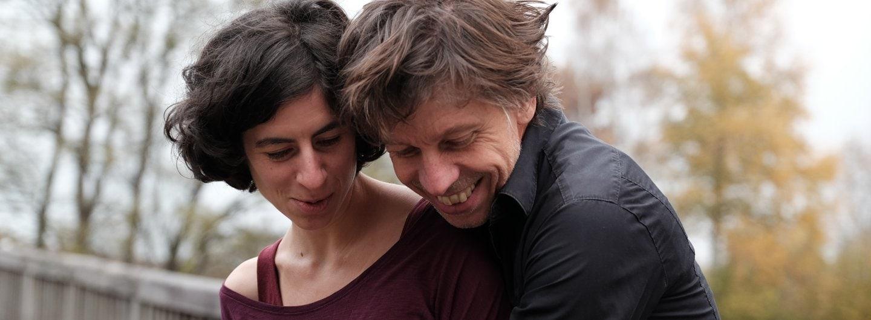 Tanzpaar in Umarmungshaltung auf Brücke. Im Hintergrund Bäume. Sie steht vor ihm mit dem Rücken zu ihm. Beide schauen zu Boden und lachen