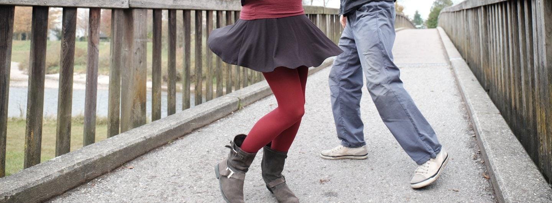 Ein Tanzpaar ab der Hüfte abwärts auf einer Brücke. Er steht in einer Grätsche und trägt weiße Sneaker zu einer ausgewaschenen blauen Hose und schwarzem Hemd. Sie trägt eine rote Seidenstrumpfhose, einen schwarzen Rock bis mitte Oberschenkel und graue wadelhohe Stiefel. Beide sind in Schrittstellung, er nach links, sie nach rechts. Dabei fliegt ihr Rock. Sie steht räumlich vor ihm