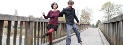 Tanzpaar auf Brücke im Hintergrund weißer Himmel und Bäume. Sie steht auf seiner rechten Seite, in seinem ausgestrecktem rechten Arm, er blickt zu Boden. Sie strahlt in die Kamera, hat die rechte Hand gen Himmel gerichtet und ihr linkes Bein knickt sich um das rechte Standbein. Beide lachen