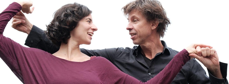 Tanzpaar vor weißem Himmel. Er steht hinter ihr, beide Hände sind in Schulterhöhe gefasst und die beiden lächeln sich an