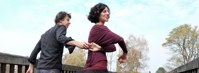 Tanzpaar auf Brücke im Hintergrund blauweißer Himmel und Bäume. Ihn sieht man hauptsächlich von hinten. Sie steht auf seiner rechten Seite, und dreht sich gerade aus ihrem linken Arm, der mit seinem gestreckten rechten Arm verbunden ist. ihr rechter Arm ist über ihrer Brust gekreuzt. Beide lächeln