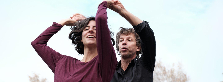 Tanzpaar vor bläulichem Himmel und Bäumen. Sie steht mit dem Rücken zu ihm, ihre Hände sind gefasst. Die Hände sind alle in der Luft über ihrem Kopf. Sie lacht er schaut konzentriert