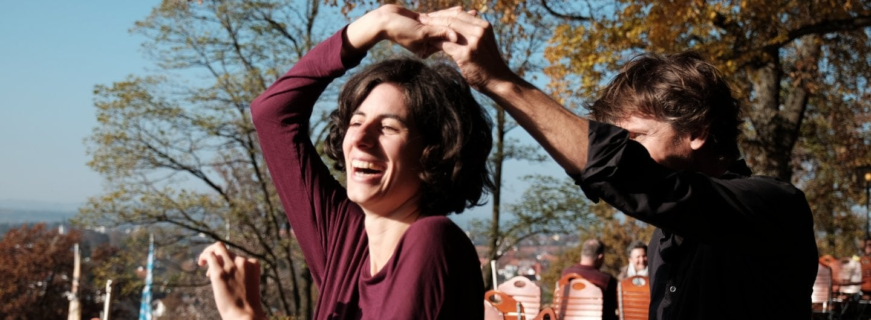 Tanzpaar im Biergarten, sie dreht unter seinem Arm durch und lacht dabei von Herzen