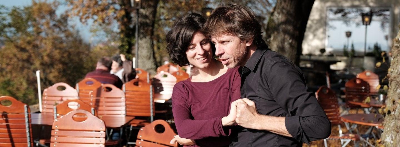 Tanzpaar im Biergarten, er hat sie an seiner rechten Seite, sie hat die Arme vor dem Körper überkreuz und er hält sie an beiden Händen gefasst
