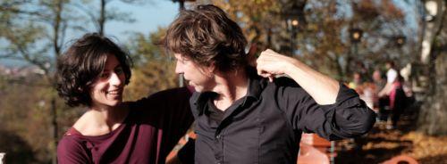 Tanzpaar im Biergarten, sie steht auf seiner rechten Seite, beide schauen sich an, er hat ihre Hand hinter seinem Kopf gefasst