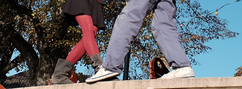 Die Beine eines Tanzpaares in Tanzpose. Im Hintergrund blauer Himmel und goldene Laubbäume. Sie trägt eine rote Seidenstrumpfhose, einen schwarzen Rock bis mitte Oberschenkel und graue wadelhohe Stiefel. Er trägt weiße Sneaker zu einer ausgewaschenen blauen Hose. Die Beiden stehen auf einer Mauer. Beide stehen sich gegenüber und machen gerade einen Schritt aufeinander zu, er mit links, sie mit rechts