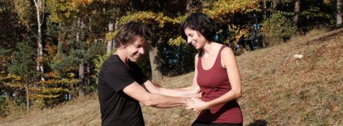 Tanzpaar am Hang im Hintergrund herbstliche Laubbäume. Das Paar steht sich gegenüber und hat im Vordergrund die Hände gefasst, im Hintergrund berühren sich mehr die Arme. Beide schauen zum Boden
