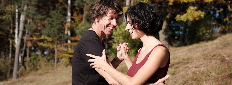 Tanzpaar in geschlossener Tanzhaltung, sommerlich gekleidet, auf einem Hang im Hintergrund herbstliche Laubbäume