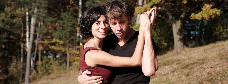 Tanzpaar sommerlich gekleidet, auf einem Hang, im Hintergrund herbstliche Laubbäume. Sie sind in geschlossener Tanzhaltung, sie eng an seine rechte Seite geschmiegt, die gefassten Hände sind steil nach oben gehalten. Sie schaut lächelnd in die Kamera, er zum Boden