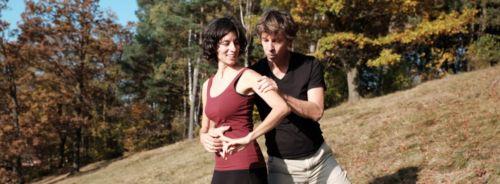 Tanzpaar, sommerlich gekleidet, auf einem Hang im Hintergrund herbstliche Laubbäume. Sie steht vor ihm, ihre rechte und seine linke Hand ruhen auf ihrem Bauch, seine linke Hand greift ihren linken Oberarm. Sie sind einander zugeneigt