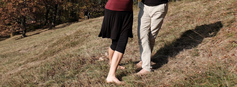 Ein brauner Grashang auf dem ab der Hüfte abwärts ein Tanzpaar zu sehen ist. Er trägt eine helle Hose, sie eine schwarze 3/4-Leggins und einen schwarzen Rock, dazu ein dunkelrotes Oberteil. Beide sind barfuß. Er steht in Schrittstellung, der re Fuß nach vorne. Sie stehen sich gegenüber in Schrittstellung auf die Kamera zu, aber die Oberkörper zueinander verdreht