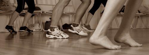 Laufende Füße auf Laminatboden in Turnschuhen und barfuß. Zum Teil nackte Beine, zum Teil sind Leggings zu sehen Im Hintergrund sind Stühle und zum Teil Taschen