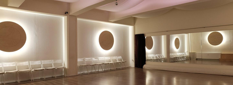 Tanzraum in atmosphärischer Beleuchtung. Der Blick ist in eine Zimmerecke. An der rechten Wand ist eine Spiegelfront angebracht, an der linken sind zwei Stuhlreihen durch eine Säule voneinander getrennt. In den Wandnieschen über den Stühlen hängt jeweils eine runde Lampe, die von hinten die Wand bestrahlt. An der Decke sind Stoffbahnen in Wellen aufgehängt.