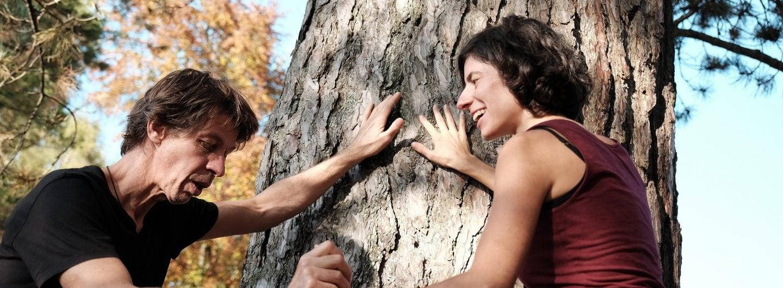 Tanzpaar sommerlich gekleidet vor einer Kiefer, die Hände gefasst, die anderen Hände am Baum angelehnt strahlen sich die beiden an. Sie sind im Profil zu sehen