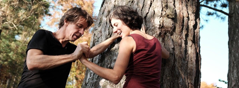 Tanzpaar sommerlich gekleidet vor einer Kiefer, die Hände gefasst, die anderen Hände am Baum angelehnt beide schauen zum Boden. Sie sind im Profil zu sehen