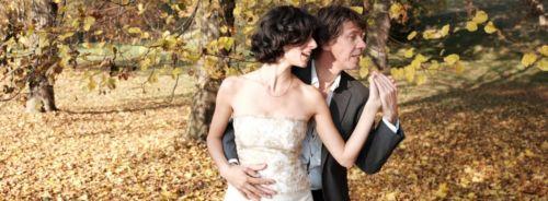 Tanzpaar im goldenen Herbstlaub. Sie steht mit dem Rücken zu ihm, an ihn geschmiegt. Ihre beiden rechten Hände liegen auf ihrem Bauch die anderen sind in Schulterhöhe gefasst. Beide schauen nach links