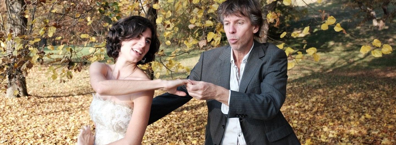 Tanzpaar im goldenen Herbstlaub. Sie steht auf seiner rechten Seite,. Ihre linke Hand ist mit seiner an ihrer rechten Taille gefasst, die anderen gefassten Hände sind vor ihrem Körper in Schulterhöhe gefasst. Sie lacht, er spitzt die Lippen