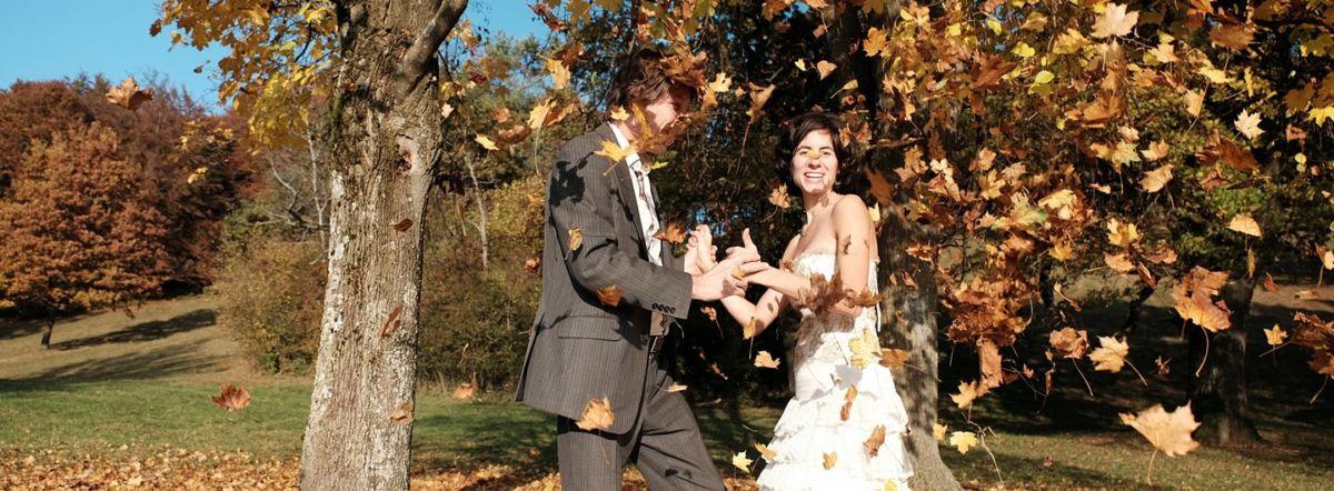 Ein Paar in Ballkleidung, das sich an den Händen fasst. Es wird von Laub beworfen. Im Hintergrund sind goldene Herbst-Laubbäume