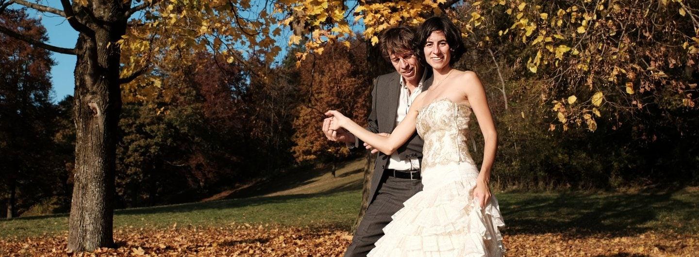 Tanzpaar im goldenen Herbstlaub. Sie steht mit dem Rücken zu ihm vor ihm, hält mit der linken Hand ihren Rock und die rechte Hand ist mit seiner in Brusthöhe seitlich gefasst. Sich schaut in die Kamera, er zu Boden.