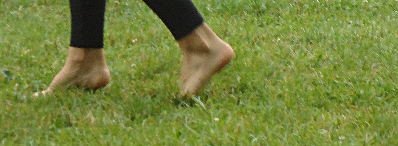 Grüne Wiese darauf gehen 2 nackte Füße in schwarzer Leggings