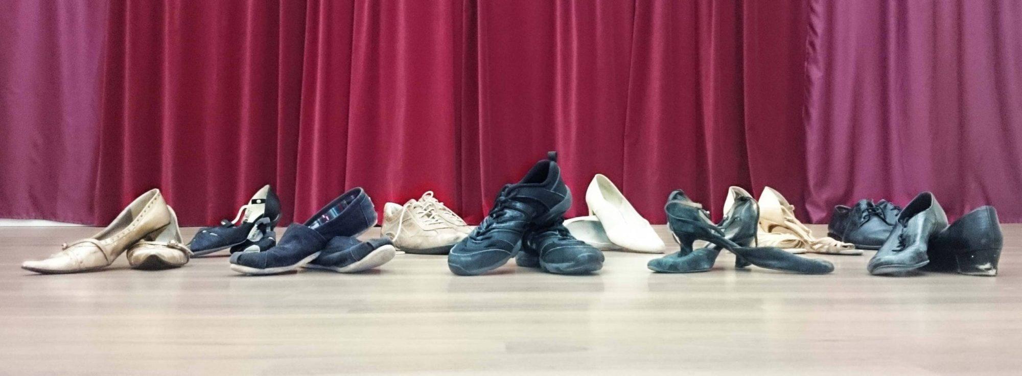 verschiedenste Tanzschuhe in zwei Reihen hintereinander aufgestellt. Sneakers, flache Schuhe, Absatzschuhe...