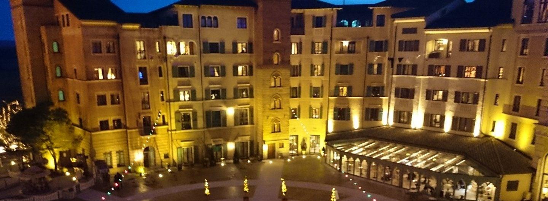 Nachts Blick von einer höheren Etage des Hotels Colosseo im Europapark Rust. In den Innehnof, auf die gegenüberliegende Häuserfront mit warmem Licht beleuchtet und Lichterketten. Im Hintergrund der dunkelblaue Nachthimmel