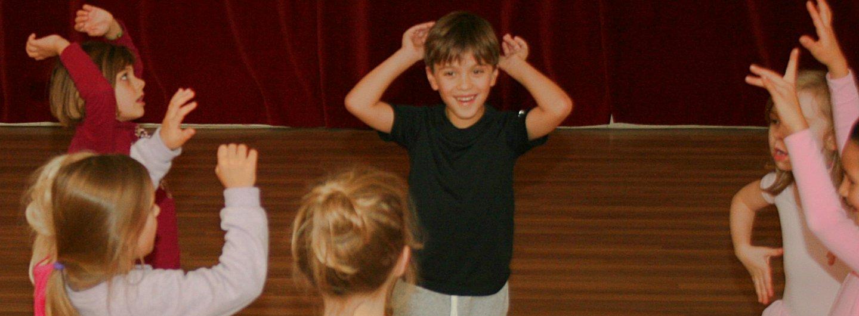 In einem Raum halten tanzende Kinder ihre Arme nach oben