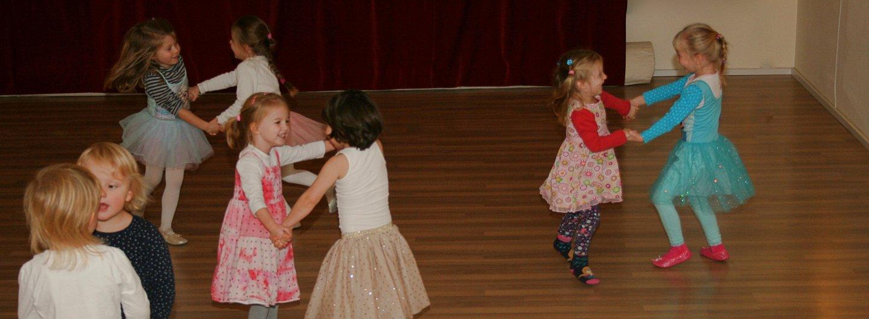 tanzende Kinder im Alter von 3-5 Jahren halten sich in Zweiergruppen an beiden Händen gefasst und drehen sich im Tanzraum